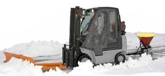 Heftruck aan het sneeuwschuiven. De banden van een heftruck zijn uitermate geschikt voor spikes.